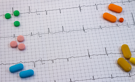 Pills and medicines of different colors and sizes on an electrocardiogram. Drugs for human consumption.