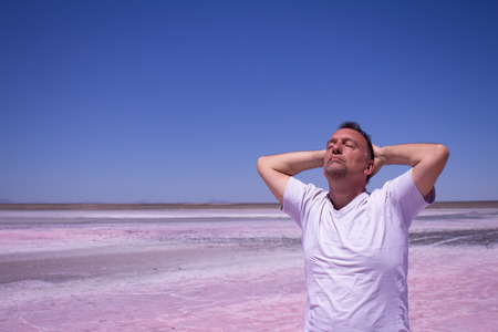 Man with his hands behind his head and his eyes closed in a salt.