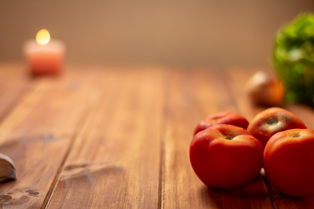 Rustic kitchen table, some tomatoes in the foreground and in the background some foods out of focus. Resource for designers.
