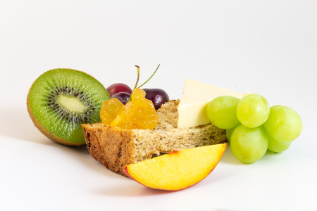 Fresh fruits for breakfast, wholemeal bread, cheese, peach, cherries, kiwi, grapes, etc. on white background.
