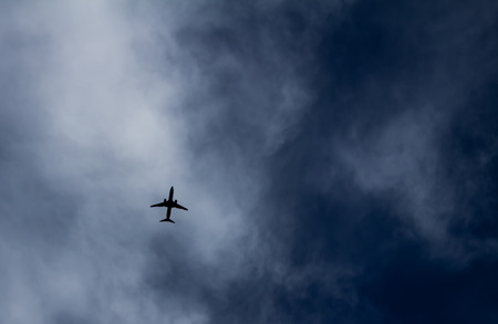Silhouette of commercial airplane with clouds in the background. Transportation of people. Standard-Bild
