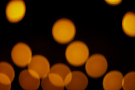 Blurry warm lights on a black background with rounded shapes. City lights. Resource for graphic design. Imagens