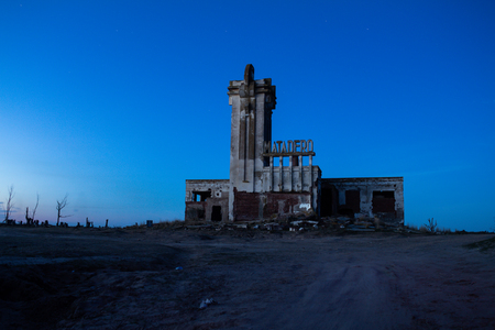 Dead trees in the abandoned city of Epecuen. Famous building to slaughter cattle. Sign that says