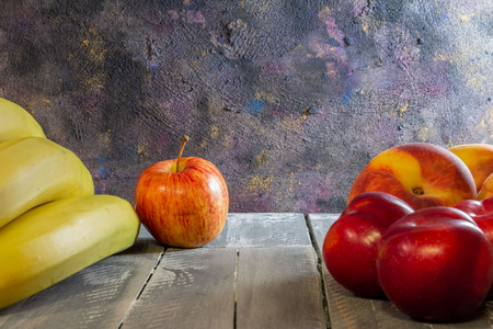 Rustic table with colorful fruits. Dark food on wooden background. Horizontal format Free space for designers. Copy space.