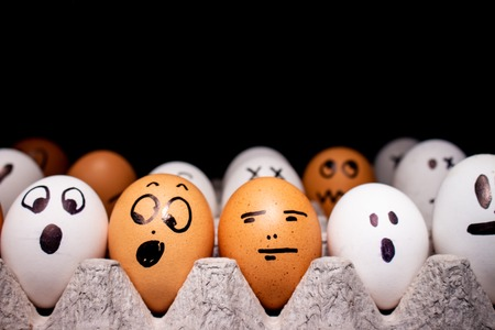 Eggs with funny expressions simulating human faces on a black background to write. Concept of ethnic diversity and moods. 免版税图像