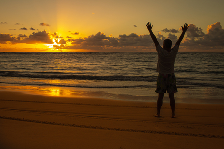 Sunrise on the coast. A man extends his arms to heaven. Landscape of warm tones. Concept of energy and vitality.