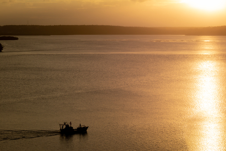 During sunset, a small barge navigates the lake. Landscape of warm tones.