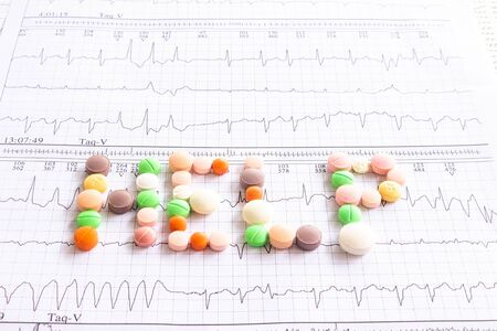 """The word """"help"""" written with colored pills on electrocardiogram strips. Concept of uncertainty and drug addiction. Medical office. Doctor bewildered."""