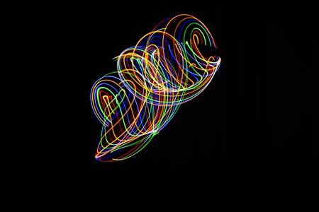 Long exposure photography made with multicolored light paint on black background, waves, curves and swirls, curvilinear or rounded pattern.