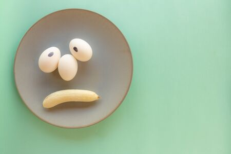 Funny face made with food. Eggs forming eyes. Mouths shaped like bananas. Food humanization. Neutral background. Free space to write. Conceptual image