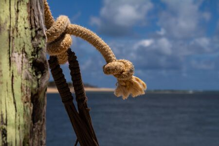Colored ropes knotted on a pole. Knots at the edge of the sea. Tying and knotting concept. Marine objects.