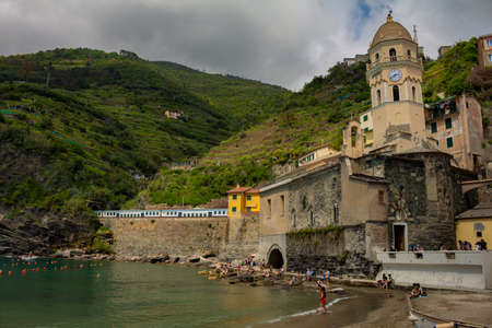 Cinque Terre, Italy. May 15, 2018. Cathedral of the coastal town of northern Italy. Tourists at the edge of the sea and the train entering the tunnel on the mountain.