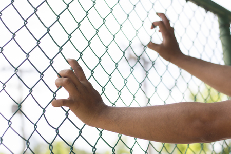hands holding fence Stock Photo