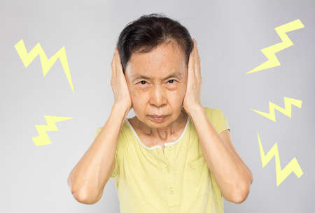 old asian woman feel  annoyed and covered her ears with her hands and felt noisy with the surrounding sounds