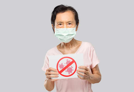 asian old woman wearing a mask holding an anti-virus banner