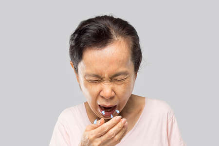 old asian woman due to cough spread saliva and sore throat