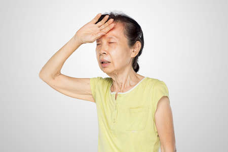 old asian woman touched her forehead feel fever and sick in white background