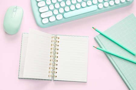 flat lay green color computer and stationery on pink pastel floor background Stok Fotoğraf