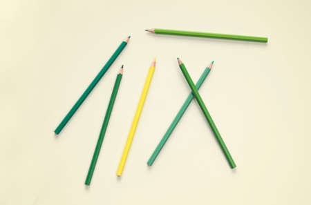 flat lay green color pencil stationery on yellow pastel floor background