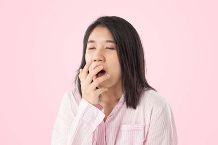 young asian woman wear pink pajamas yawn feeling sleepy on pink pastal background