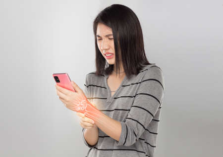 asian young woman holding mobile feel wrist bones pain in gray background