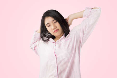 young asian woman wear pink pajamas yawn and stretch when her wake up feeling sleepy Stock fotó