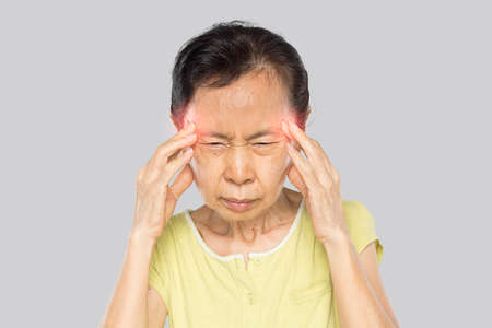 old asian woman arms raised touch her head feel headache in gray background Stock fotó