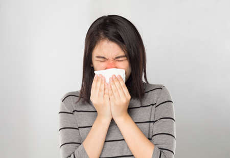 young asian woman feel sick covered her mouth with tissue while sneezing