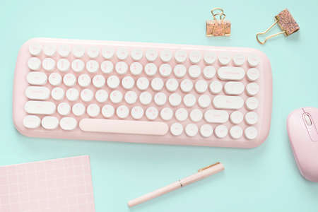 flat lay pink color computer and stationery on mint green pastel floor
