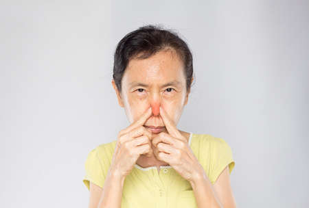 old asian woman pinched her nose due to the bad smell