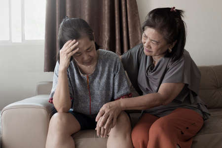 old asian woman suffering from mental health depression have comforting from friend
