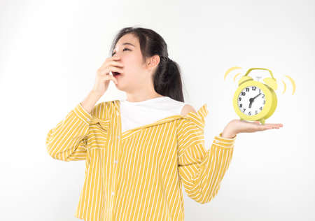 young asian woman yawn and holding alarm clock feeling sleepy Stock fotó