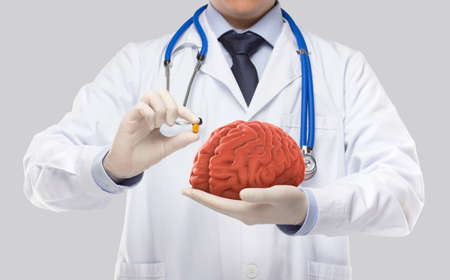 doctor holding brain and tonic in gray background Stock fotó