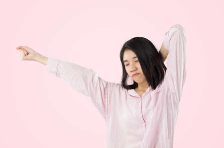 young asian woman wear pink pajamas yawn and stretch when her wake up feeling sleepy Stok Fotoğraf