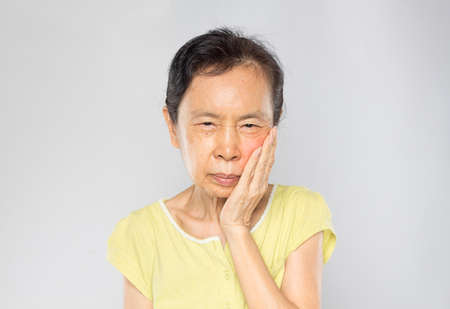 old asian woman feels toothache in gray background