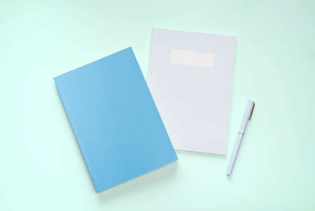 flat lay blue color book and stationery on green pastel floor Stok Fotoğraf