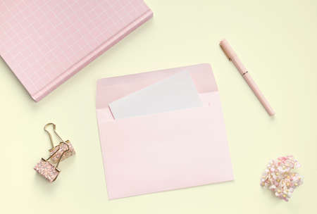 flat lay pink book stationery and letter in yellow backgroung