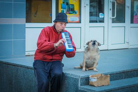 poor man: Pobre hombre sentado en estilo y tocar la arm�nica con el perro en Zhitomir, Ucrania, el 23 de septiembre de 2013. Editorial