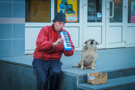 harmonica: Poor man sitting on stile and playing the harmonica with dog at Zhytomyr, Ukraine on September 23, 2013.
