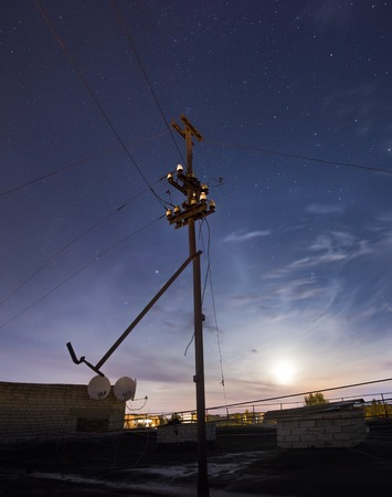 electric line: Electric line in the night with moon Stock Photo