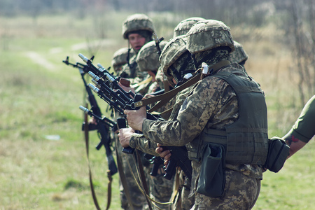 disarm: Military soldiers disarm their guns at field