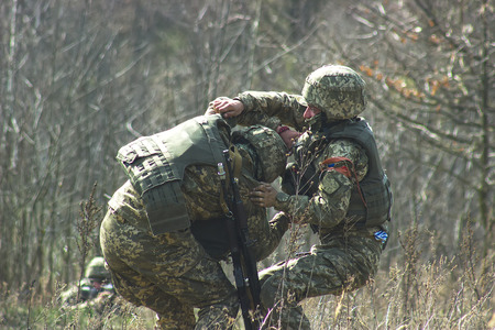 gunfire: Military bear at back his wounded friend under gunfire
