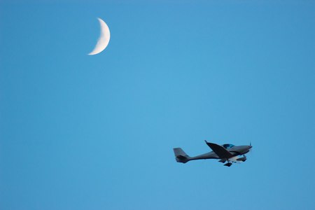Plane fly above the land near moon