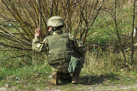 tactical: Military soldier at tactical exercises give the sign Stock Photo