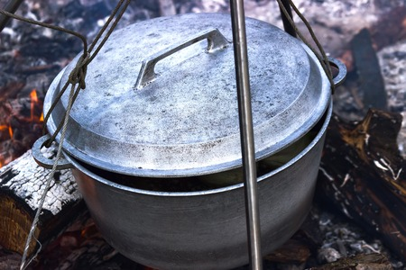 sooty: Cooking in sooty cauldron on campfire at forest