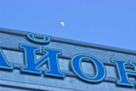 Wooden signpost with inscription against the sky with moon