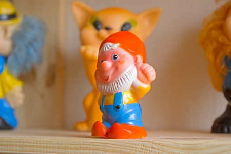 Toy gnomes on the shelf wooden background