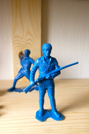miniature toy soldier on wood background, close-up Stock Photo