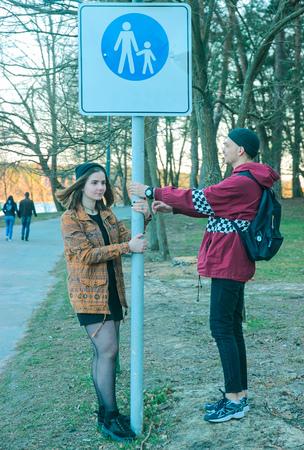 sluttish: two happy homeless man and woman fool around near street sign