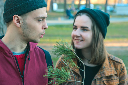 sluttish: two happy homeless man and smiling woman hold pine stick in the evening